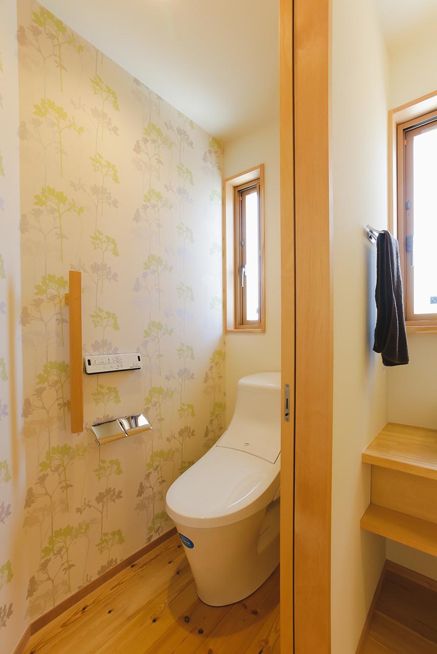 パステル調の壁紙で明るいトイレ