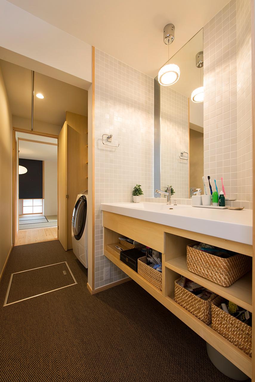 洗面台は薄いグレータイルで清潔感を演出、収納計画も抜群