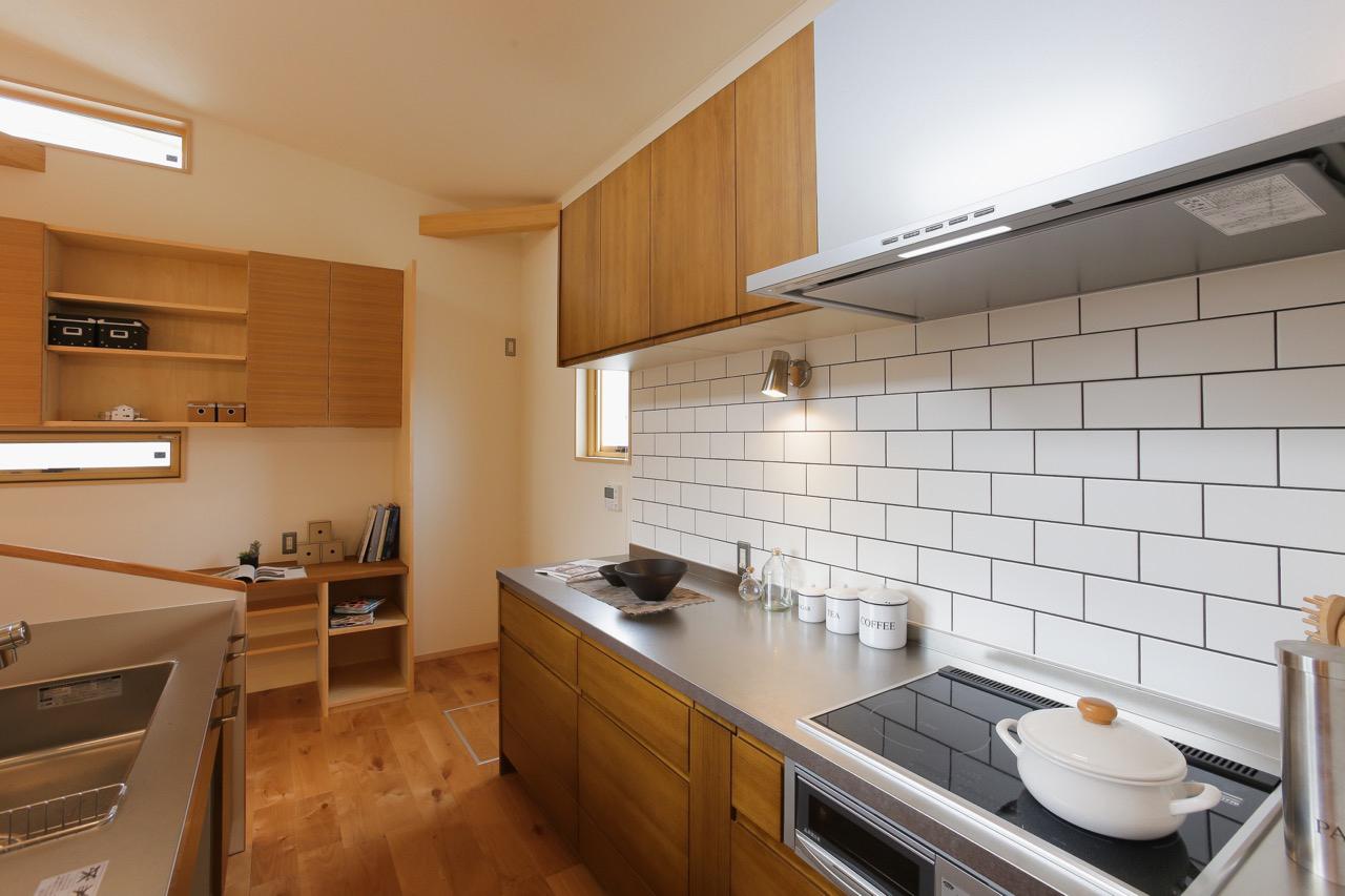 白いタイルがアクセントの2列型キッチン