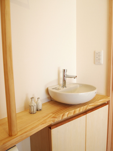 トイレの手摺カウンターに手洗い器や収納をつけてスッキリと。