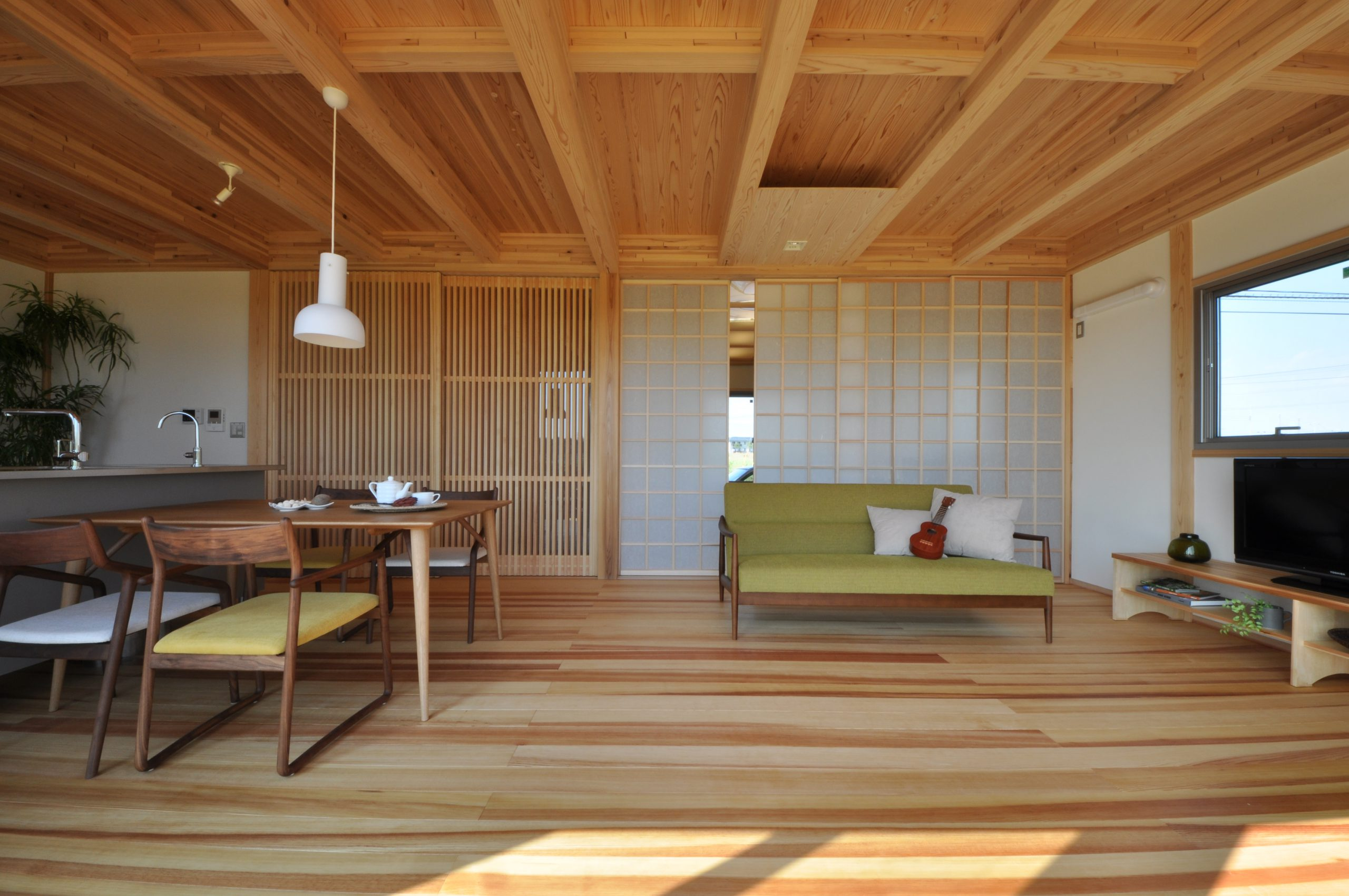 無垢材をふんだんに使い、光と風の通り道もデザインした快適なリビングの建築実例:天井の無垢材のラインと引き戸の格子が美しい