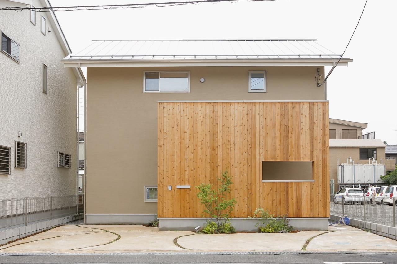 自然素材をふんだんに使った木の家の外観:エントランスの壁が無垢材を用い、壁には珪藻土の塗り壁