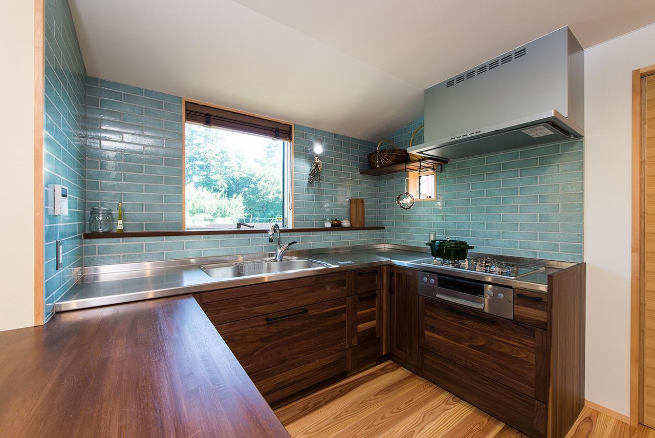 平屋のガレージハウスのキッチンの実例:ブルーのタイルとウォルナットの扉が落ちついた雰囲気のコの字型キッチン
