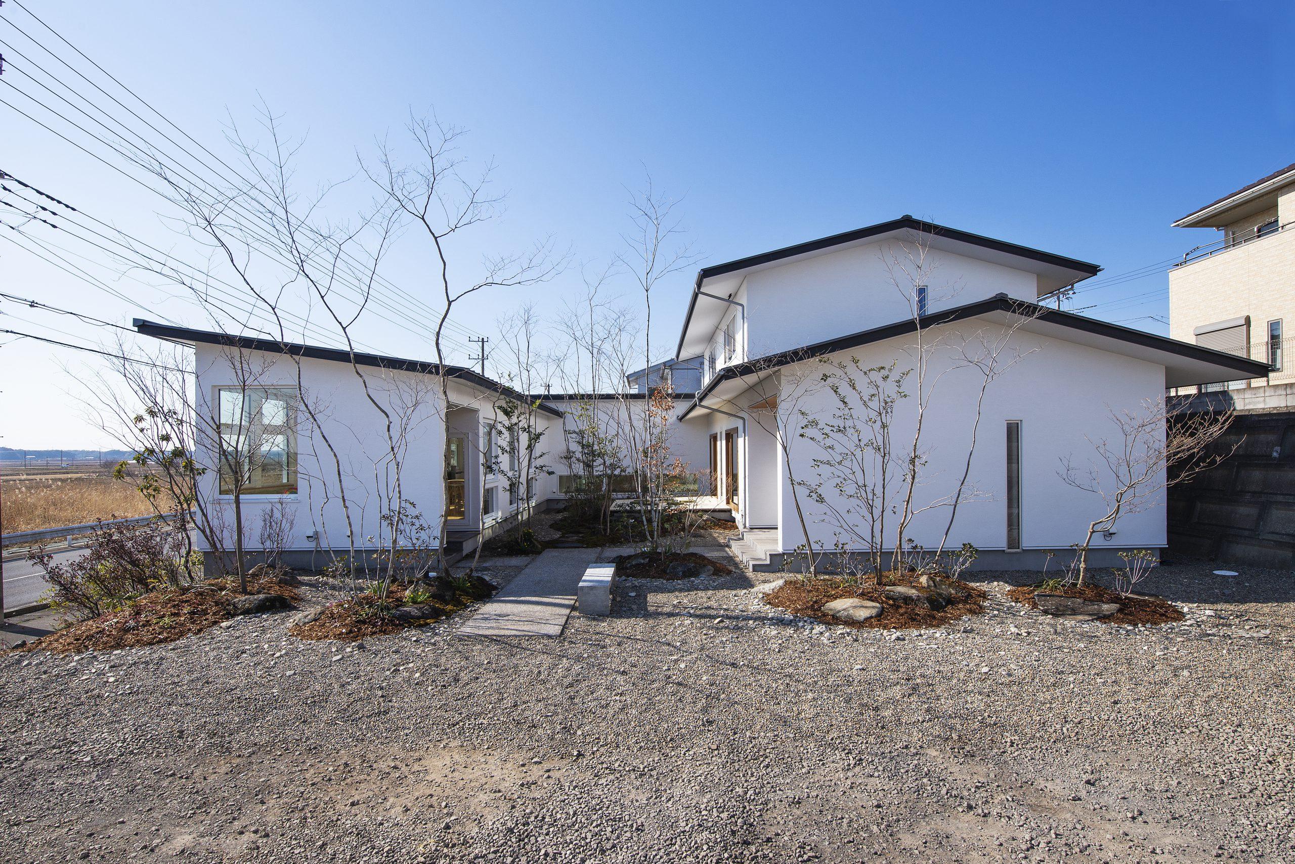 コの字型の中庭のある家の外観:白い外壁に中庭の緑が映え、包まれるような空間を実現しました