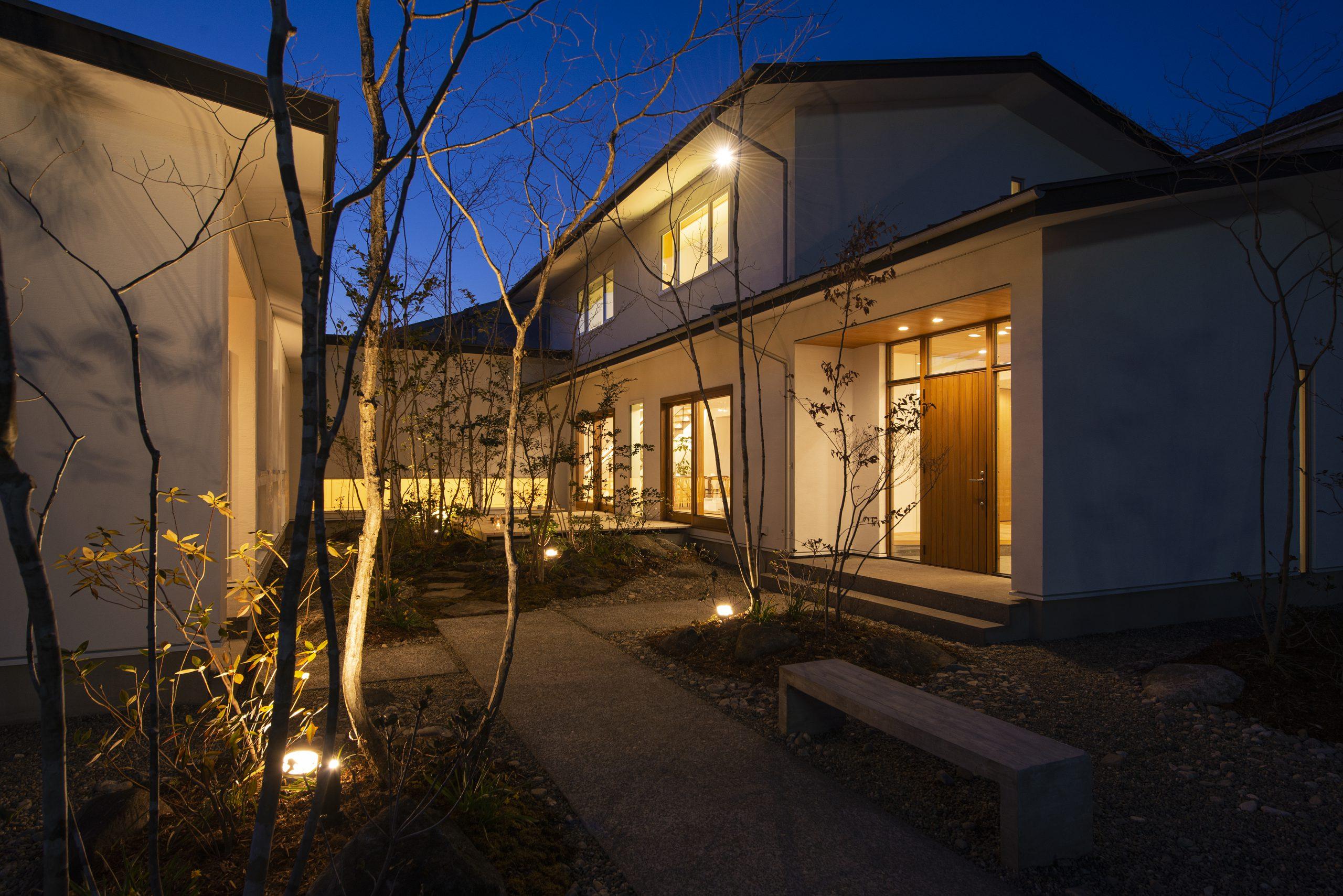中庭のある家の夜景:スポットライトが家のシルエットを植栽をやさしく照らしてほっと一息つける間取りです