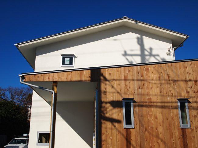 自然素材のふんだんに用いた家の外観:無垢材のエントランスと漆喰の白い外壁